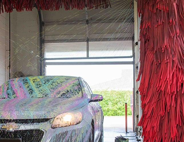 car wash chemicals being sprayed on car in carwash